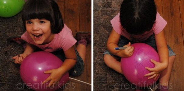 enthusiastic child drawing on balloons