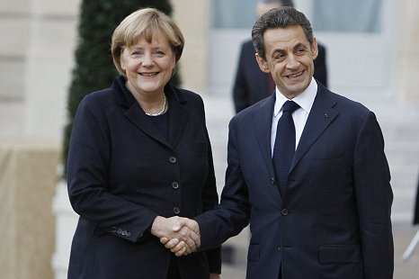 Nicolas Sarkozy and Angela Merkel shake hands after eurozone meeting