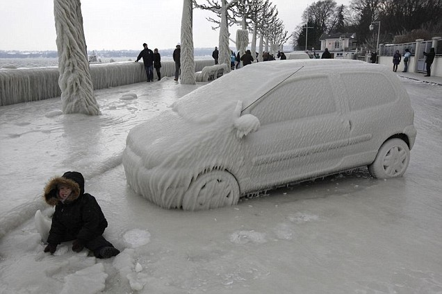 A boy sits in front of an ice covered car in Versoix near Geneva 