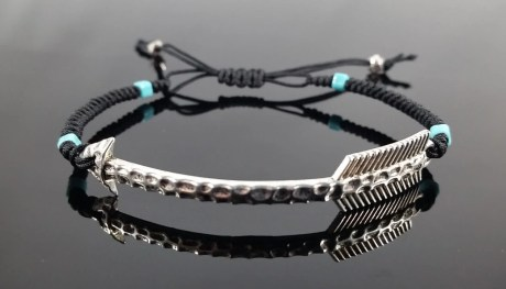 Macramé bracelet with metal arrow center piece, turquoise color beads, and silver color accents beads. Adjustable sliding knot.