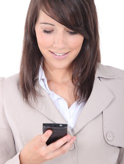 Young brunette sending message with mobile phone