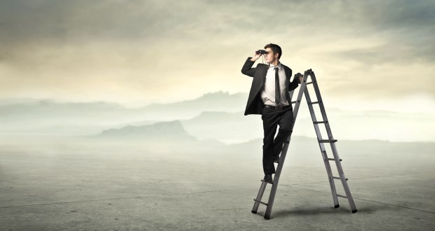 Businessman standing on a ladder and using binoculars
