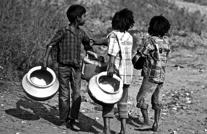 Tetulmari, Dhanbad, February 2, 2016: Boys overcome the problems of contaminated and scarce water by collecting drinking water from a damaged pipeline.