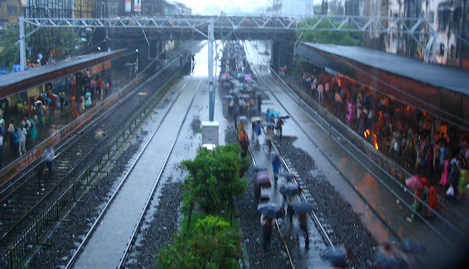 People trudge through flooded railways tracks at Grant Road station in Mumbai. (Photo by Ashwan Lewis)