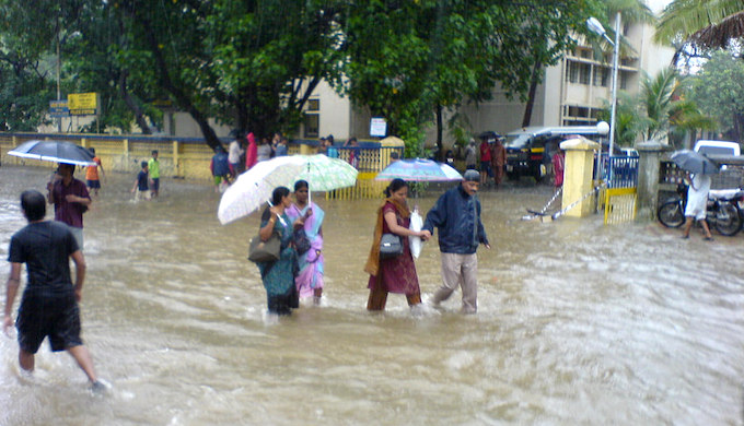 People wading through a flooded street in Kandivali, Mumbai. (Photo by Rakesh)