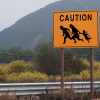 """A sign at the side of a rural highway reads """"Caution"""" families of undocumented workers may appear in road."""