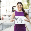 "A young woman holds up a sign that says, ""VOTE!"""