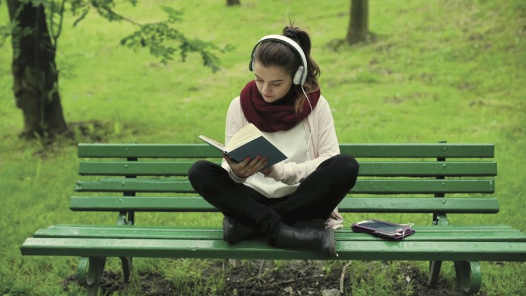 girl-listening-music-and-reading-book-in-the-park_nksvli4p__F0000