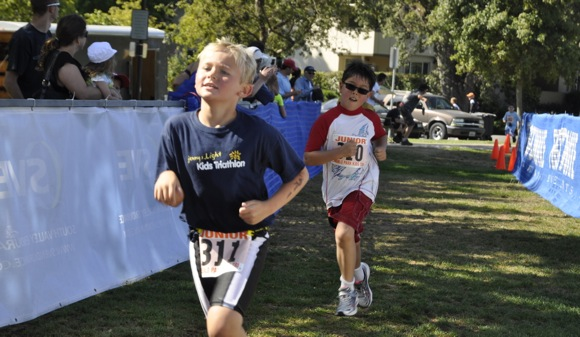 boy crossing finish line in Children's Triathlon in Menlo Park