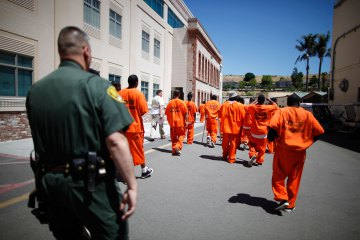 Inmates are escorted by a guard through San Quentin state prison