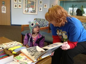 Two-year-old Eliza McKinney of Green learns about zebras and giraffes from Elaine Melvin, a children's librarian at the Portage Lakes Branch Library, after a visit with the doctor at ACHP Green on Friday.
