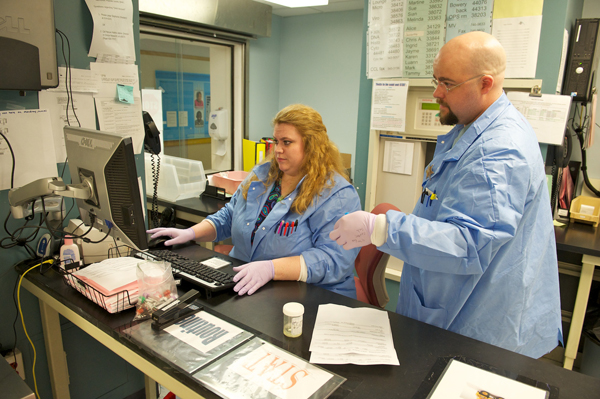 Michael Townsend and Kim Phillips confirm the patient specimen name and orders match before receiving them into the computer.