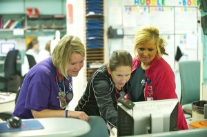 ER doctor Maria Ramundo shows nurse Kimmie Jacobs and ER coder Rebecca Stubbs something on the screen