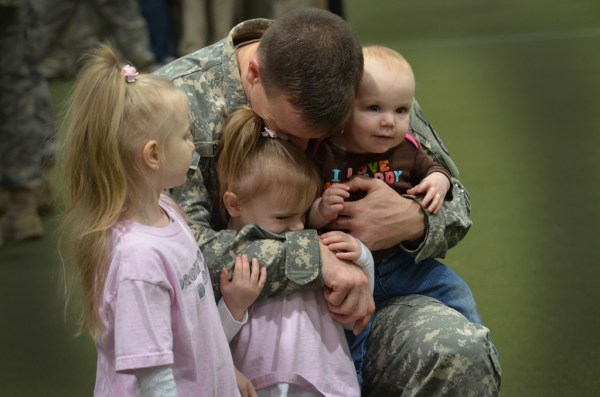 SFC William Petit hugs his children at a deployment ceremony for the HHD 210th Military Police Battalion, Michigan Army National Guard, 15 February 2012. The 72 members of the 210th are departing for their deployment to Afghanistan. Photo courtesy The National Guard