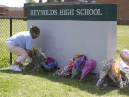 Fei Wilkening leaves flowers at a growing memorial at the entrance to Reynolds High School on Wednesday, June 11, 2014, in Troutdale, Ore. (Statesman Journal)