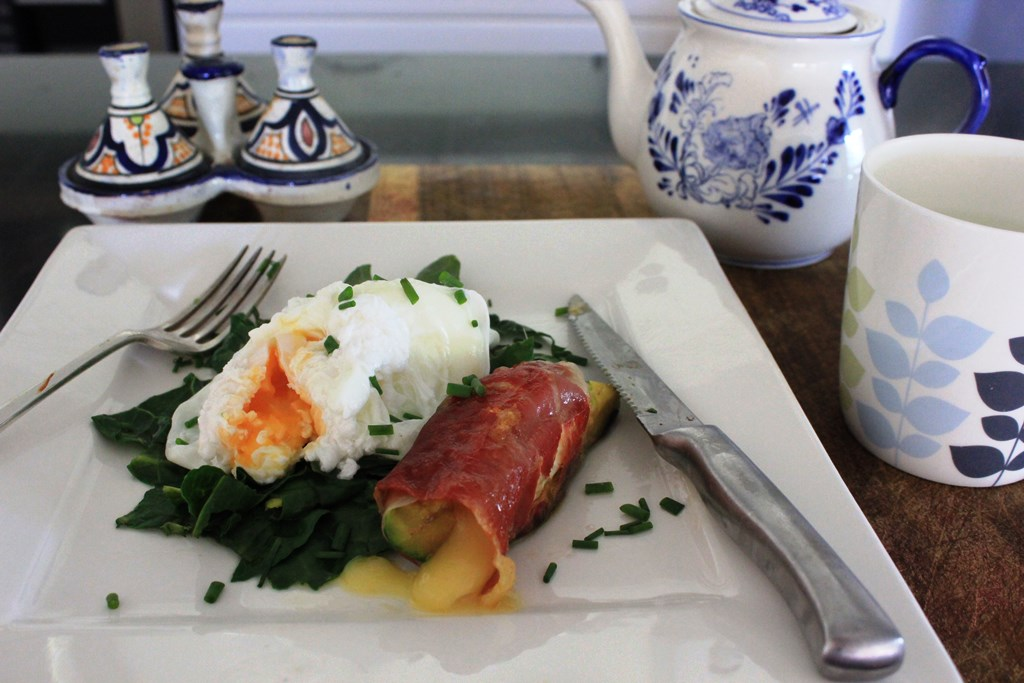 Poached eggs on wilted spinach with camembert-filled avocado wrapped in pancietta