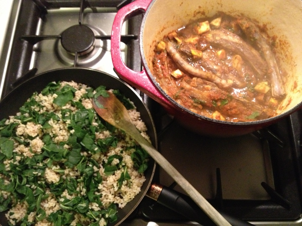 Indian curry and spinach rice cooking on stove
