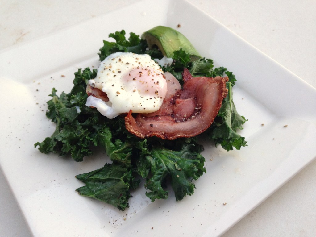 Poached egg, bacon and avocado on a bed of kale