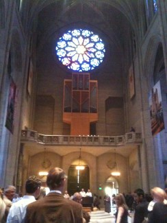 Round stain glass at Grace Cathedral above organ pipes