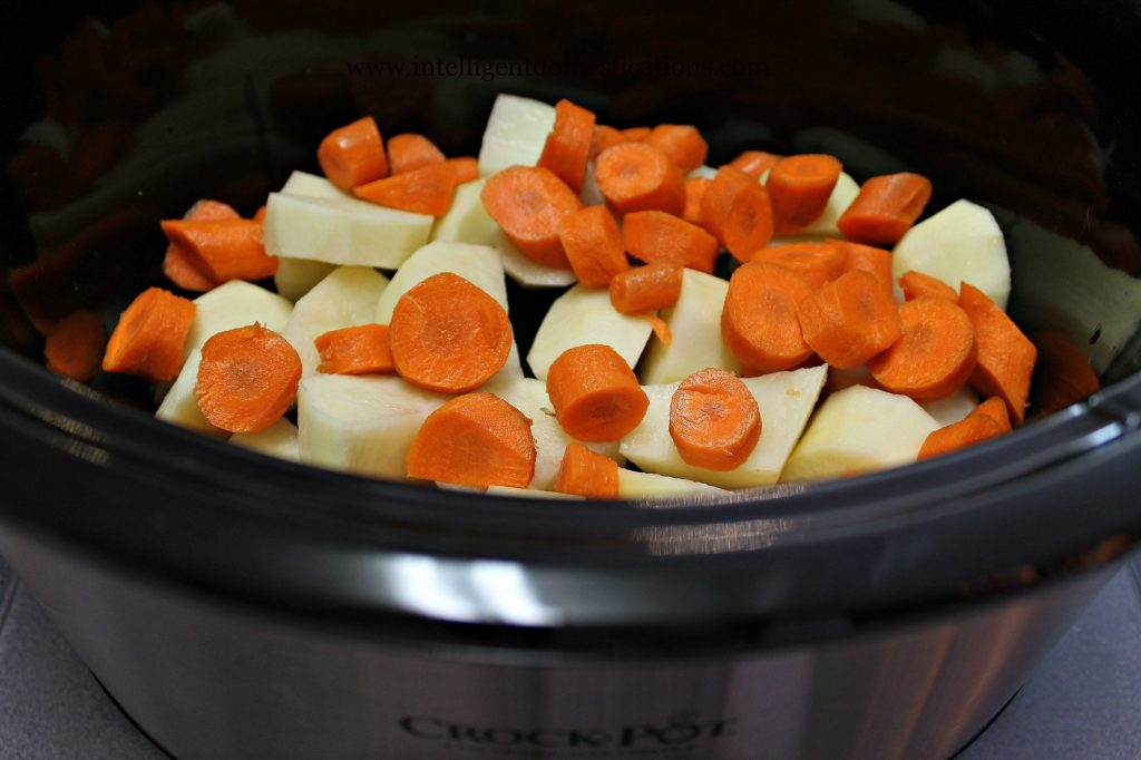 Carrots and potatoes in the bottom of the crockpot.intelligentdomestications.com