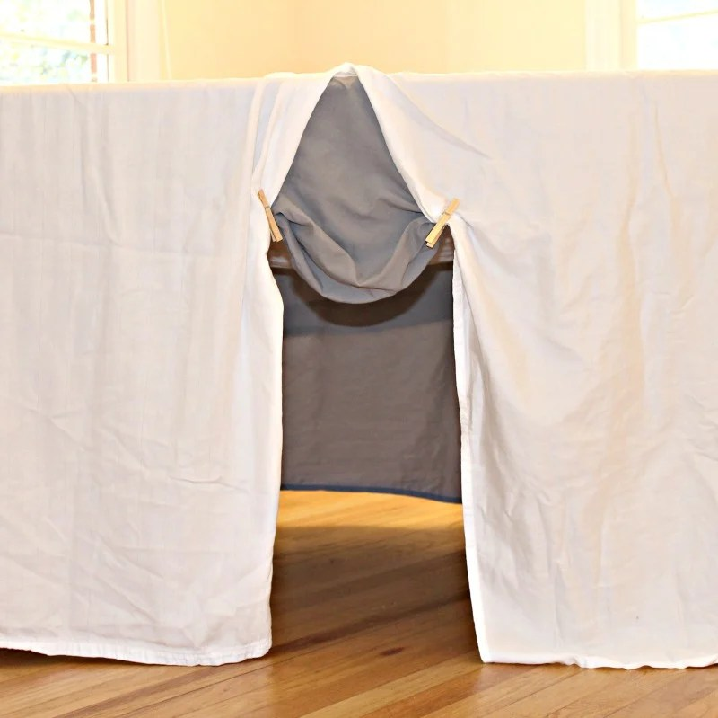 drape-the-dining-table-with-bed-linens-and-create-one-opening-using-clothespins-to-secure-the-sheets