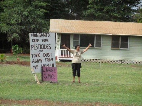 A Molokai resident expresses joy as the march passes by her home, which is located across the street from Monsanto's fields. (WNV/Imani Altemus-Williams)