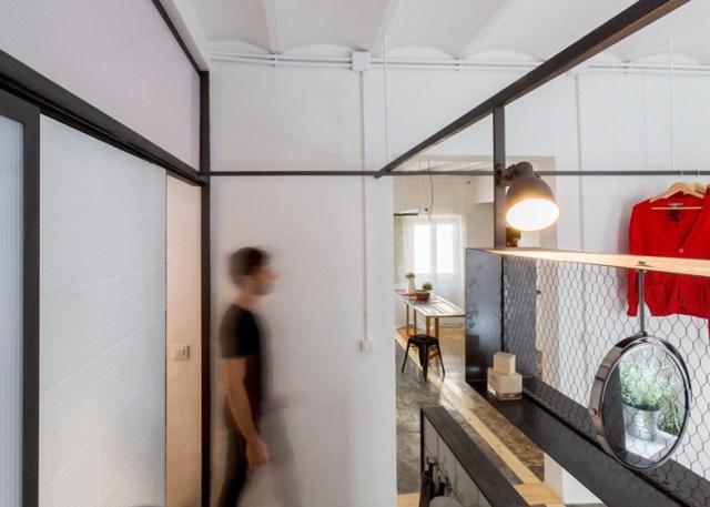 Paso del baño al dormitorio con una separación de estructura metálica y tela de gallinero.