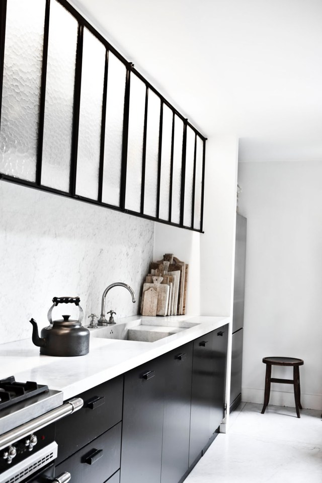 Cocina con los muebles de la parte superior en vidrio y metal lacado negro. Me gusta mucho por su sencillez y elegancia.