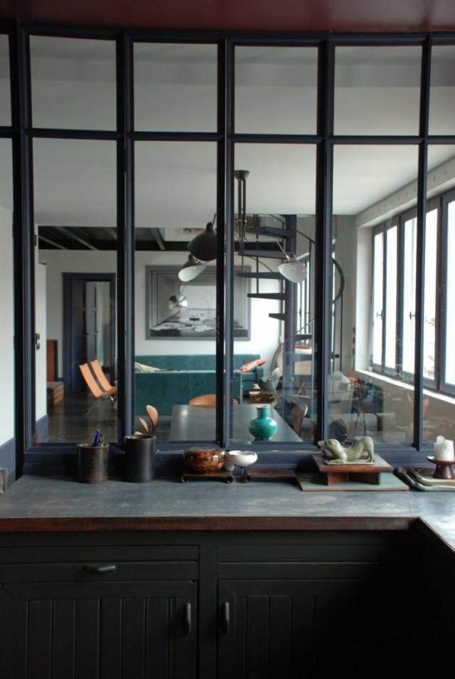 Pared de vidrio que separa la cocina del comedor con divisiones de hierro.