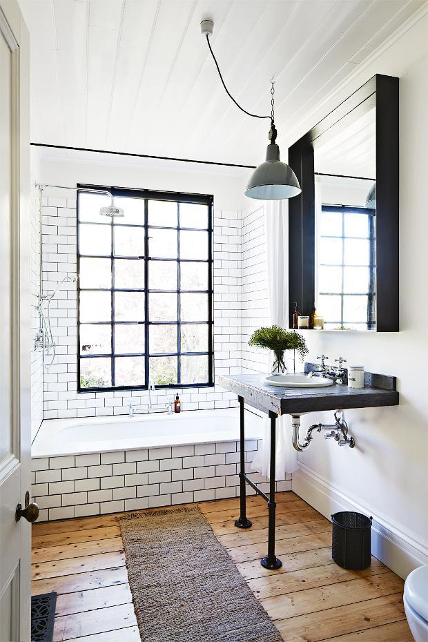 Otro baño de la vivienda con una magnífica ventana de aire industrial, con las divisiones en cuadrados y realizada en hierro negro.