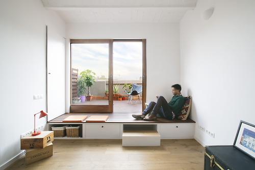 Por último, en el otro extremo de la vivienda, nos encontramos con la zona de estar, unida a la terraza por ese espacio que queda elevado y con el mismo pavimento que el exterior.