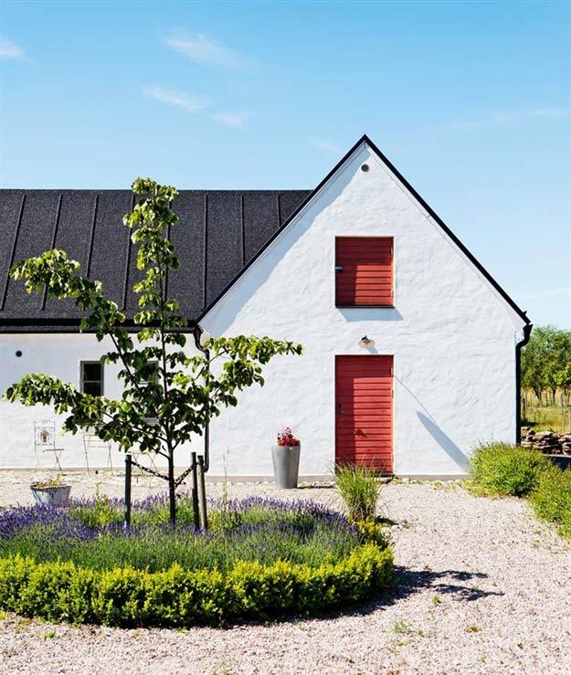 Fachada de la vivienda con una entrada de grava blanca