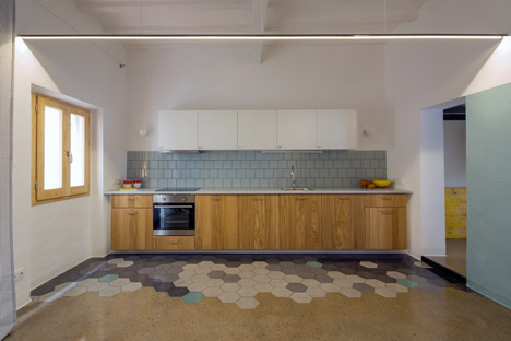 Frente de cocina hecho en una madera de pino teñida. Fijaos en el suelo, cerámica hexagonal que se encuentra de manera irregular con el pavimento continuo.