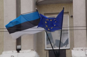 The Estonia flag flies next to the European Union flag above a building doorway in downtown Tallinn, Estonia. (Photo by Nick Shook)