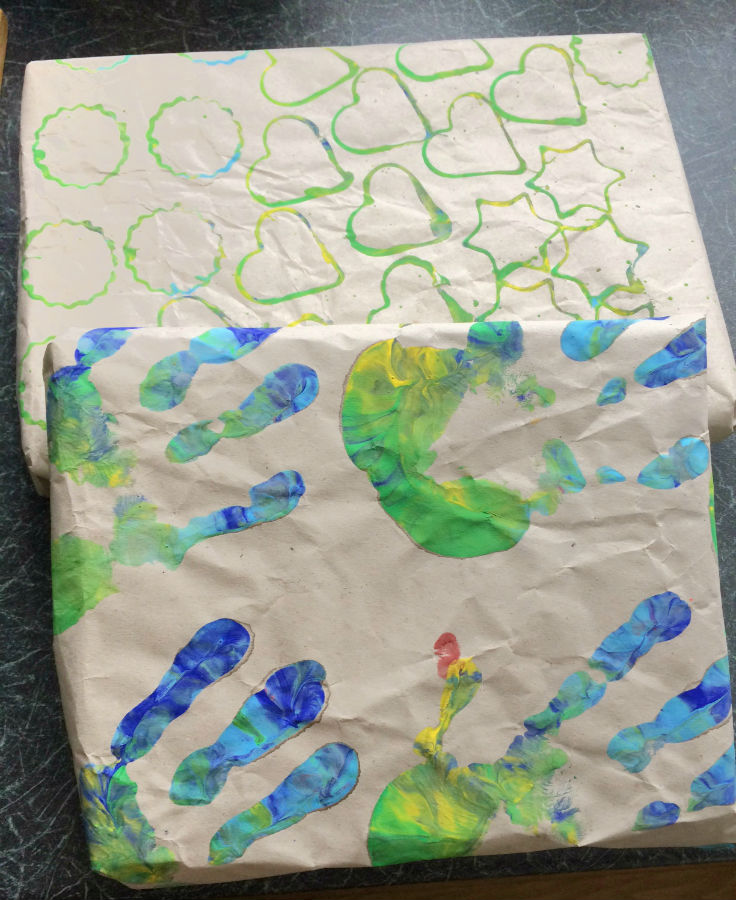 Homemade wrapping paper by children, using hand prints and cookie cutters to print with paint