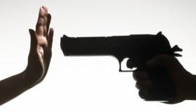 Man pointing gun at a woman making hand gesture close up