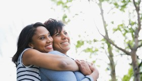 Adult woman embracing mother from behind