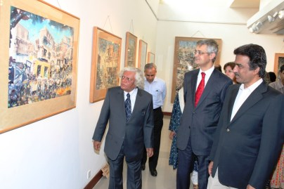The veteran artist Dr. Ajaz Anwar explains the theme behind his paintings to the Turkish Ambassador Mustafa Babur Hazlan and DG of PNCA Tauqir Nasir.
