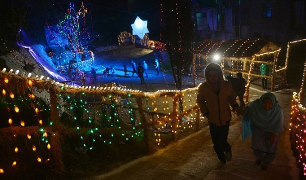 Pakistani people walk past Christmas decorations displayed in Islamabad on December 24, 2015. AFP PHOTO