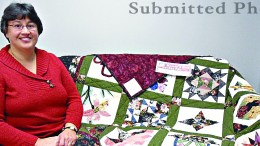 Jody Finnegan poses next to a quilt ready for the fair.