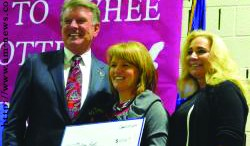 Melissa Hunt (center) receives the grant for Stoddard Elementary School from Governor Butch Otter (left).