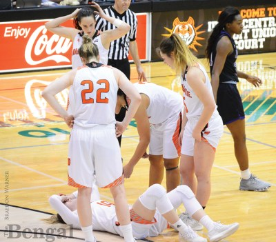 Female basketball players and ref on basketball court.