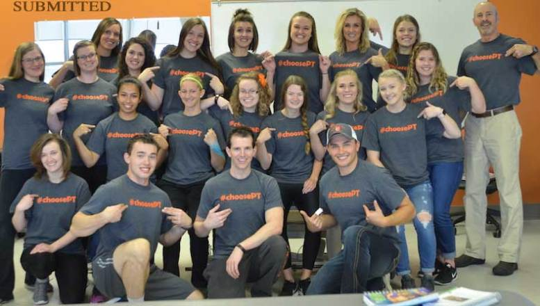 Photo of PT students showing off their #choosePT shirts.
