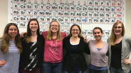 Group of students standing in front of periodic table.