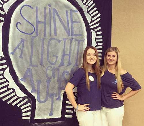 Two girls in front of a 'Shine a Light on Autism' sign