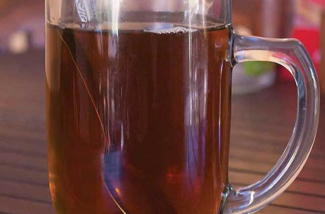 Hot buttered rum and spoon in a clear mug