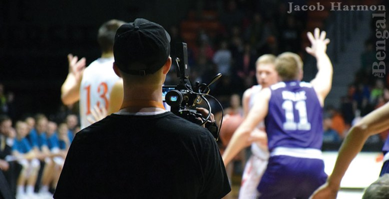 Member of sports crew videotaping a basketball game