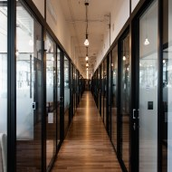 Hallways of hardwood, walls of frosted glass and black steel.