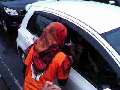 Anggota Bawaslu Jabar membagikan bunga ke seorang pengendara, Kamis (27/3). Pemberian ini dalam rangka kampanye anti politik uang dalam Pemilu 2014. (JABARTODAY/AVILA DWIPUTRA)