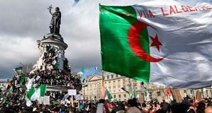 A protester waves and Algerian flag during a rally in support of the ongoing protests in Algeria against the president's bid for a fifth term in power, at Place de la Republique in Paris, on March 10, 2019.  / AFP / Bertrand GUAY